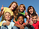group of diverse kids holding thumbs up
