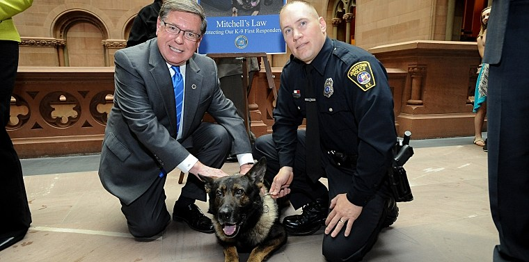Senator Seward with K-9 Mitchell and handler Jamestown Police Officer Eric Kraft during a Capitol press conference announcing support for Mitchell's Law.