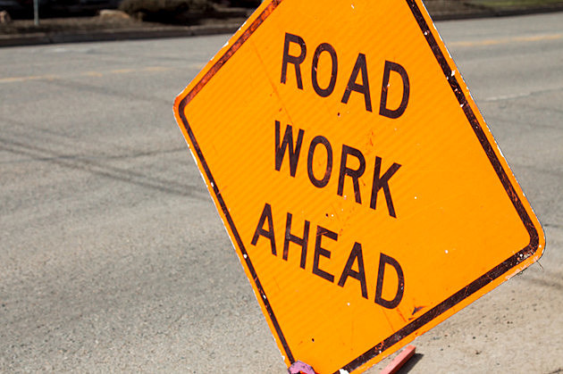 Road work ahead sign against asphalt road