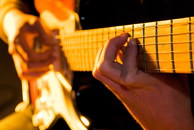 Hand playing guitar chord with shallow depth of field and orange lighting.